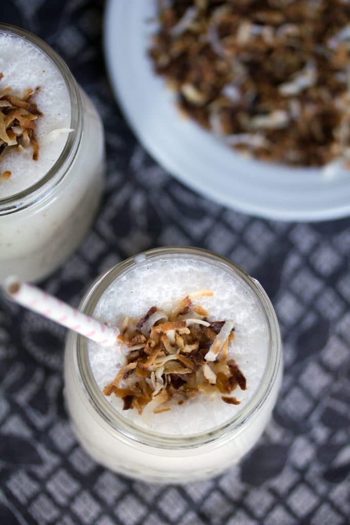 Overhead view of two vanilla coconut milkshakes topped with toasted coconut and straws with a plate of toasted coconut in the background