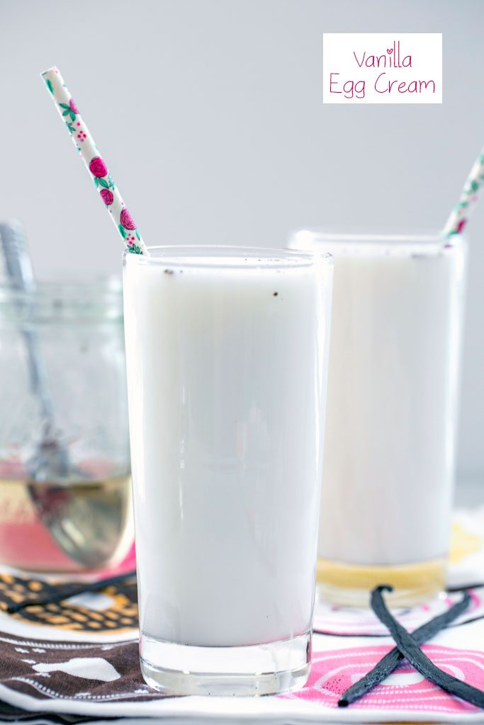 Head-on view of a tall glass of vanilla egg cream with a second vanilla egg cream, jar of simple syrup, and vanilla beans in the background with recipe title at top