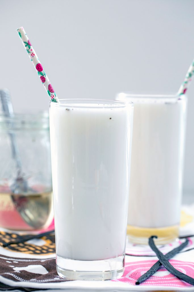 Head-on view of a tall glass of vanilla egg cream with a second vanilla egg cream, jar of simple syrup, and vanilla beans in the background