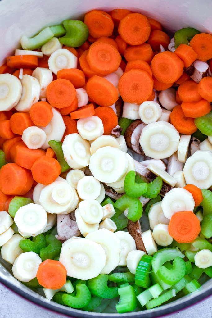 Overhead view of chopped carrots, parsnips, celery, and mushrooms in stockpot.