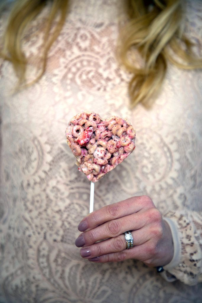 Susie's hand holding a heart-shaped Very Berry Cheerios Treats Pop in front of a pink lace shirt