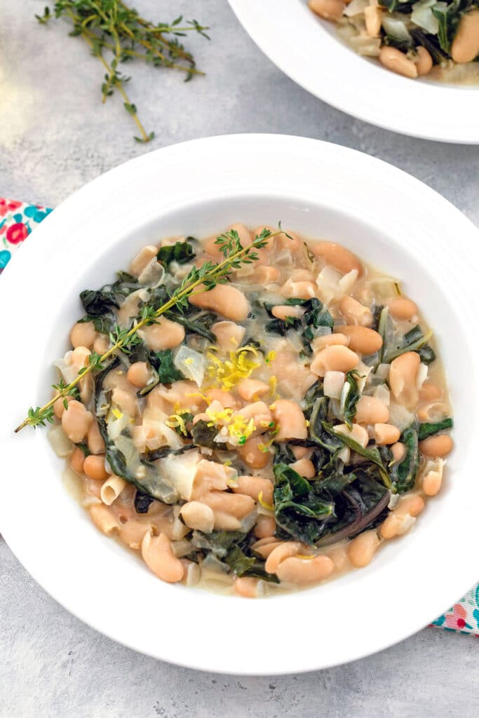 Overhead view of warm cannellini bean salad with chard, marscarpone, fresh thyme sprigs, and lemon zest