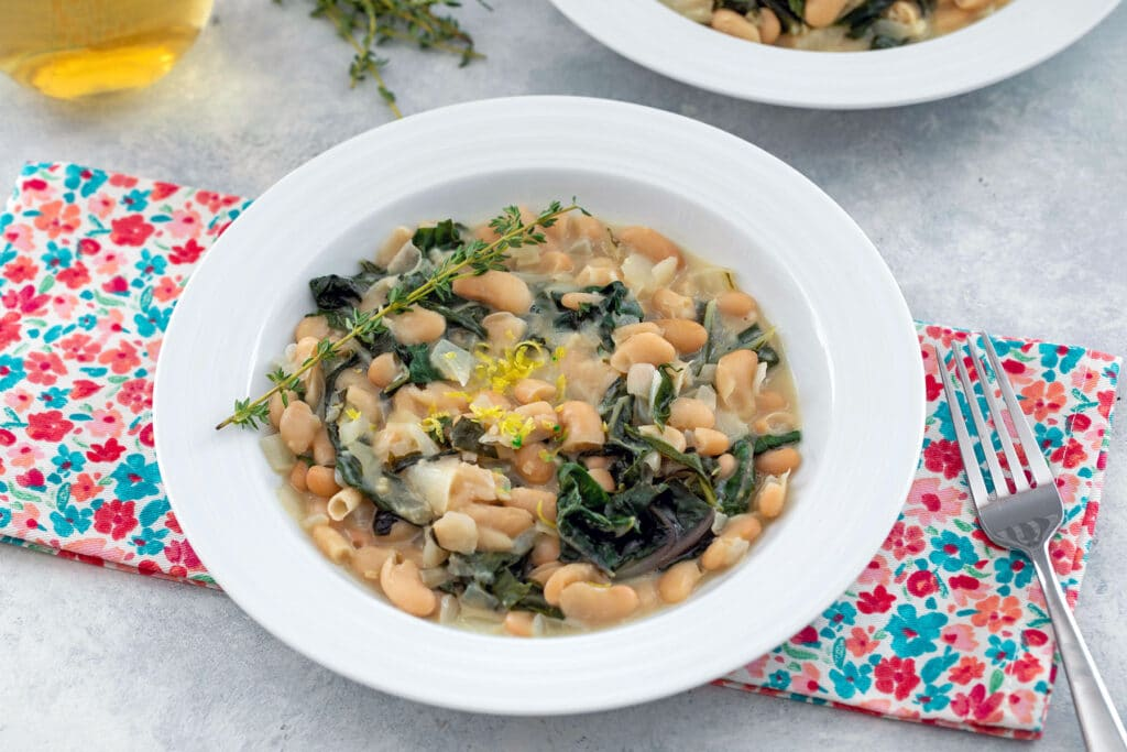 Landscape overhead view of warm cannellini bean salad with chard and mascarpone with fork and second bowl in background