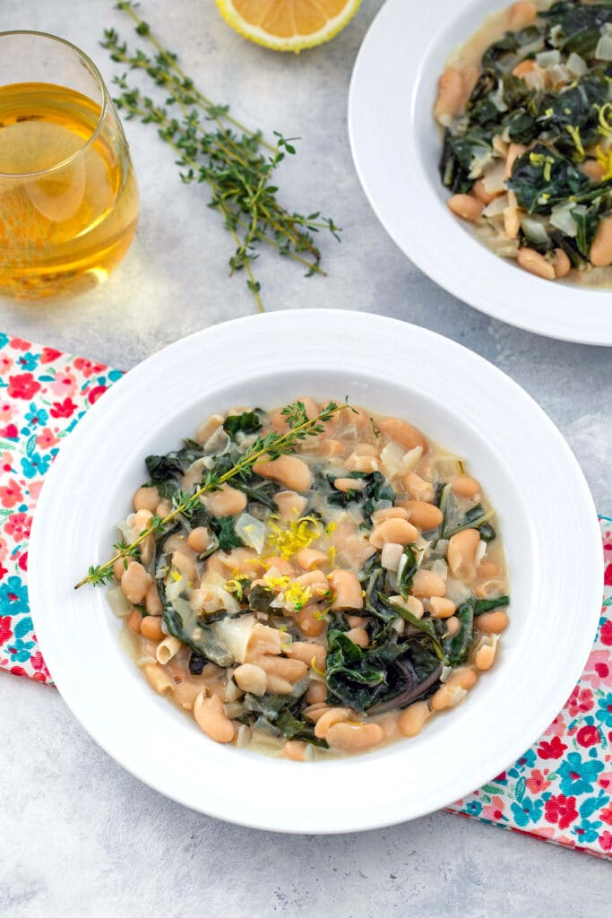 Bird's eye view of white bowl with warm cannellini salad with chard, mascarpone, thyme, and lemon zest with glass of wine, thyme sprigs and second bowl of beans in background