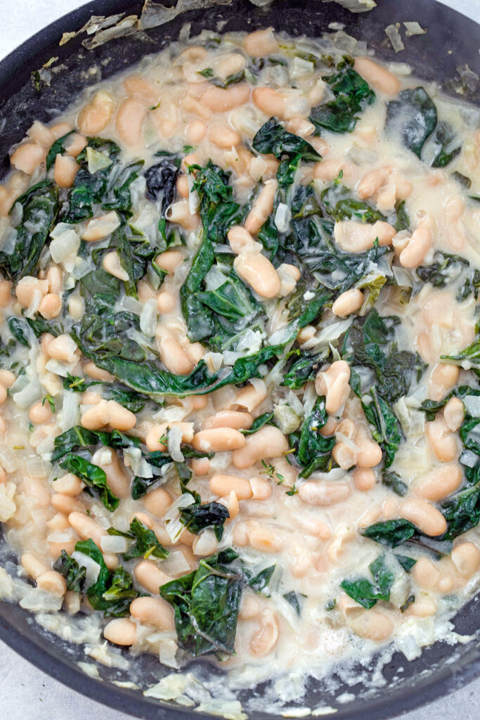 Overhead closeup view of skillet with cannellini bean salad with chard and mascarpone mixed in