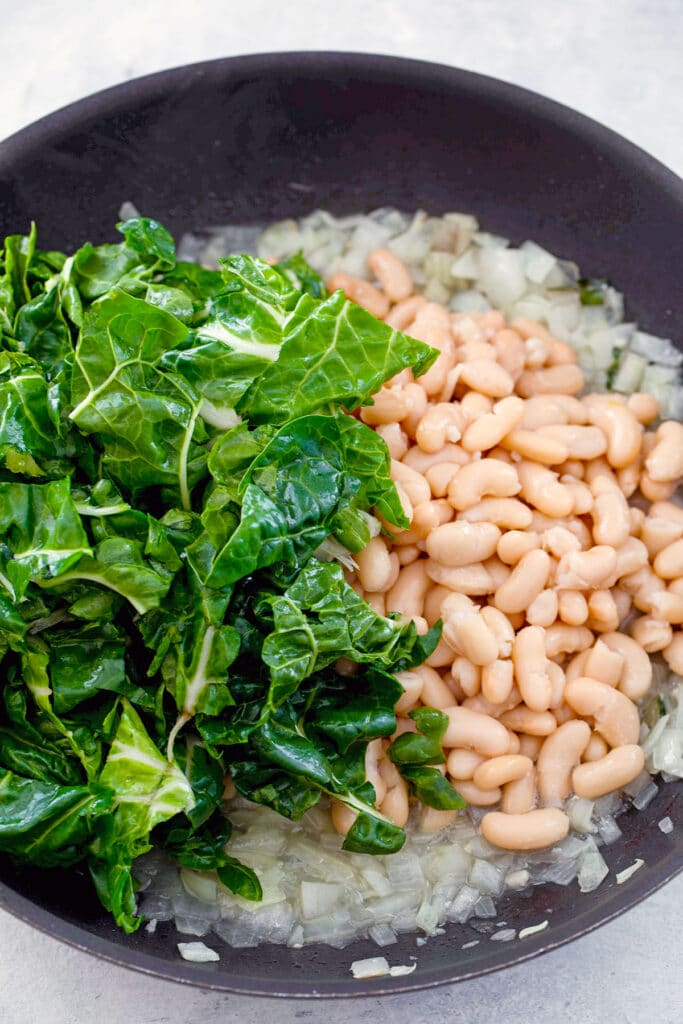 Onions cooked in skillet and topped with chard, cannellini beans, and vegetable broth
