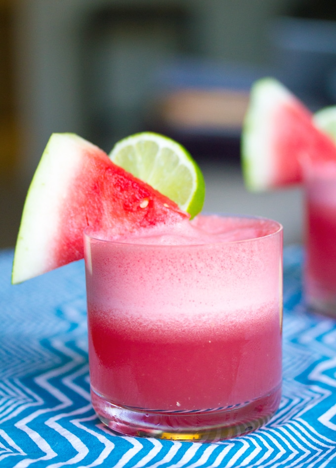 Head-on view of a watermelon coconut cocktail with watermelon wedge and lime round garnish