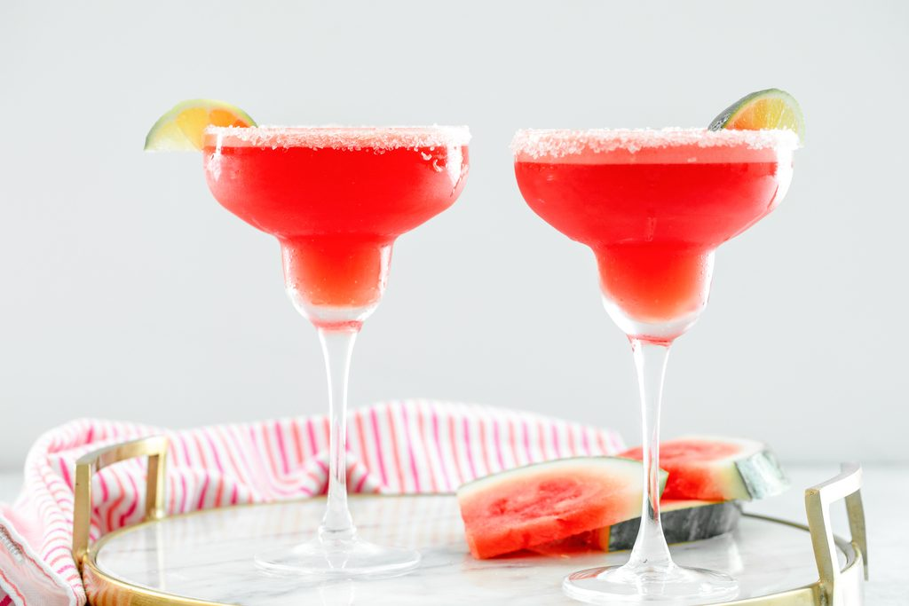 Landscape head-on view of two watermelon margaritas with sea salt rims and lime wedge garnishes on a marble tray with watermelon slices also on tray