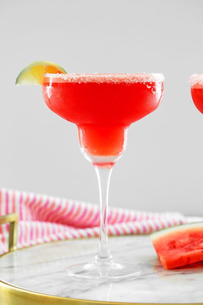 Head-on view of watermelon margarita with sea salt rim and lime wedge with watermelon slice and second margarita in background