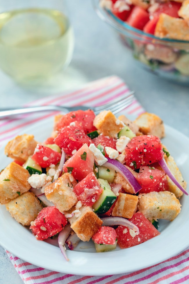 A head-on view of watermelon panzanella salad on a white plate and pink striped towel with big bowl of salad, fork, and glass of white wine in the background