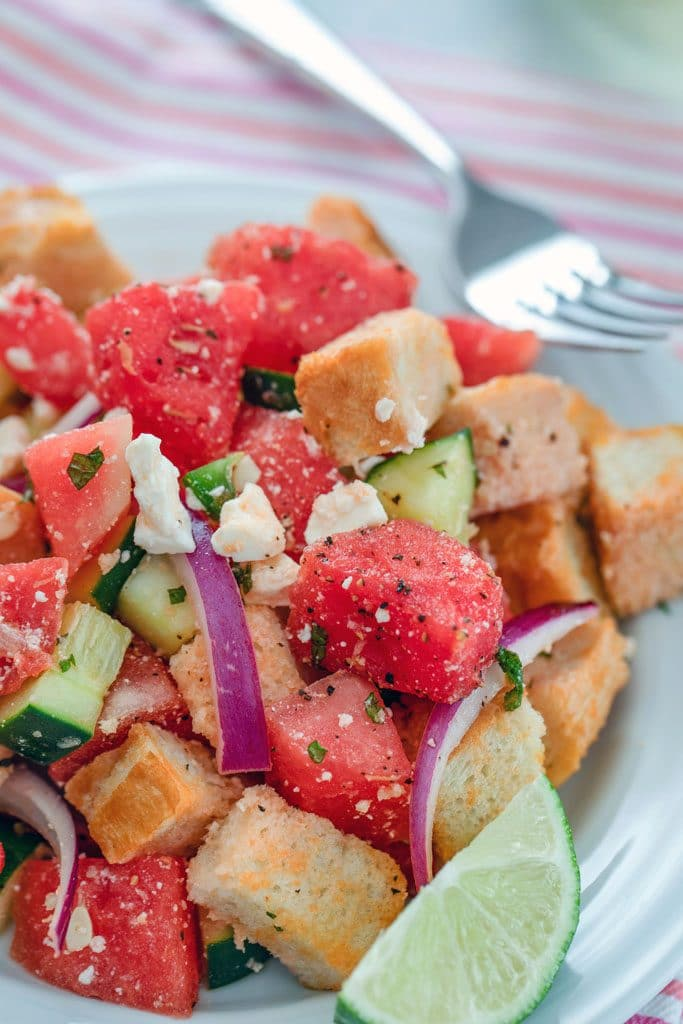 Close-up view of watermelon panzanella salad, including watermelon, red onion, cubed bread, cucumber, feta cheese, and a lime wedge