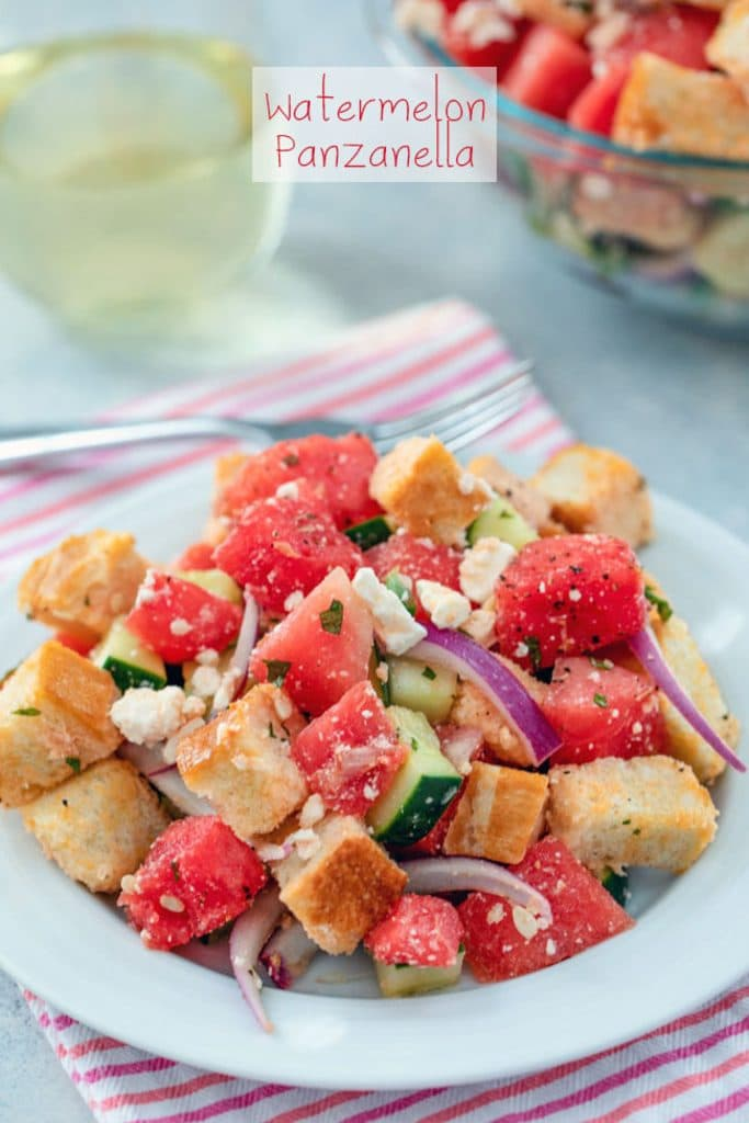 "A head-on view of watermelon panzanella salad on a white plate and pink striped towel with big bowl of salad, fork, and glass of white wine in the background and ""Watermelon Panzanella"" text at top"