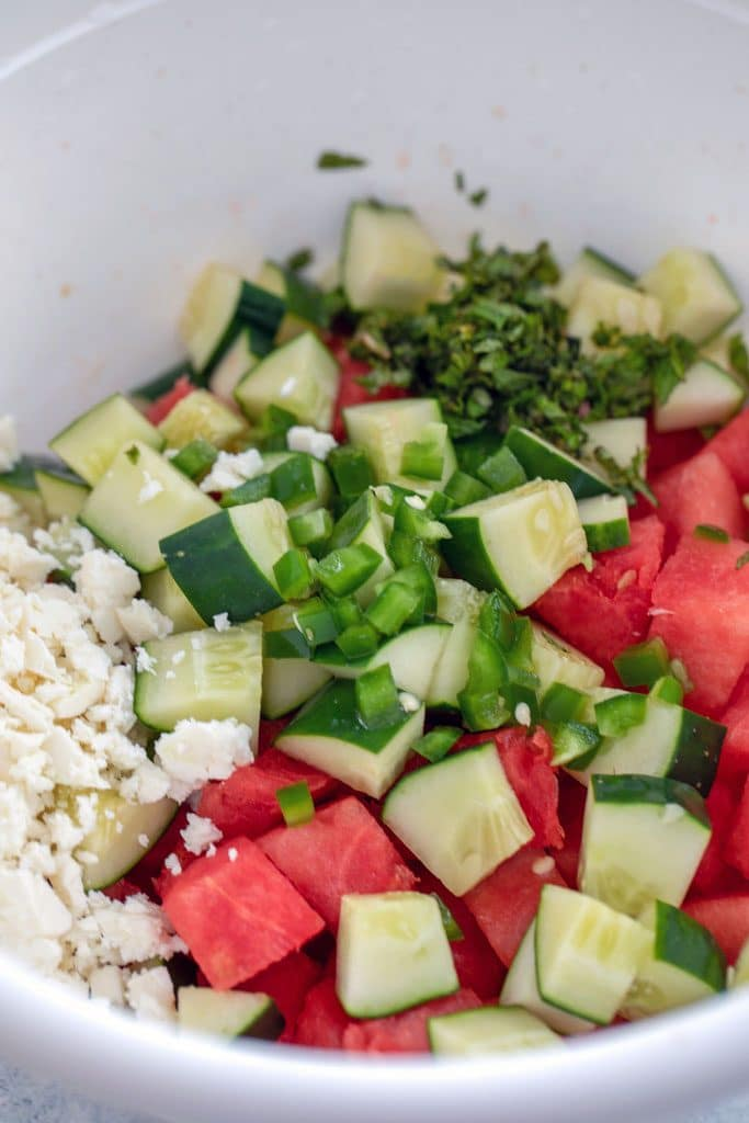 A big bowl filled with cubed watermelon, cubed cucumbers, feta cheese, diced jalapeño pepper, and chopped mint.