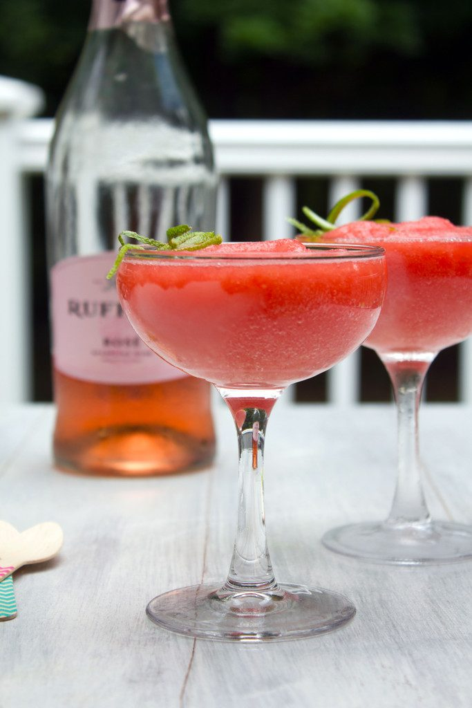 Head-on view of two coup glasses of watermelon rosé slushies on a table outside with bottle of rosé in the background