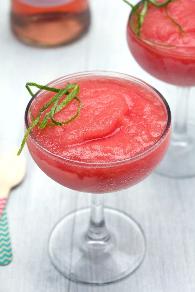 Head-on closeup view of watermelon rosé slushie with second glass in the background, wooden spoons, and bottle of rosé
