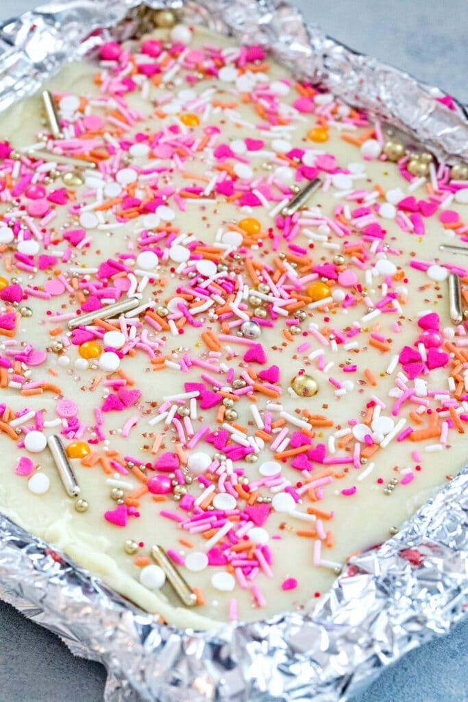 Cookie dough bars in pan with white chocolate ganache and sprinkles