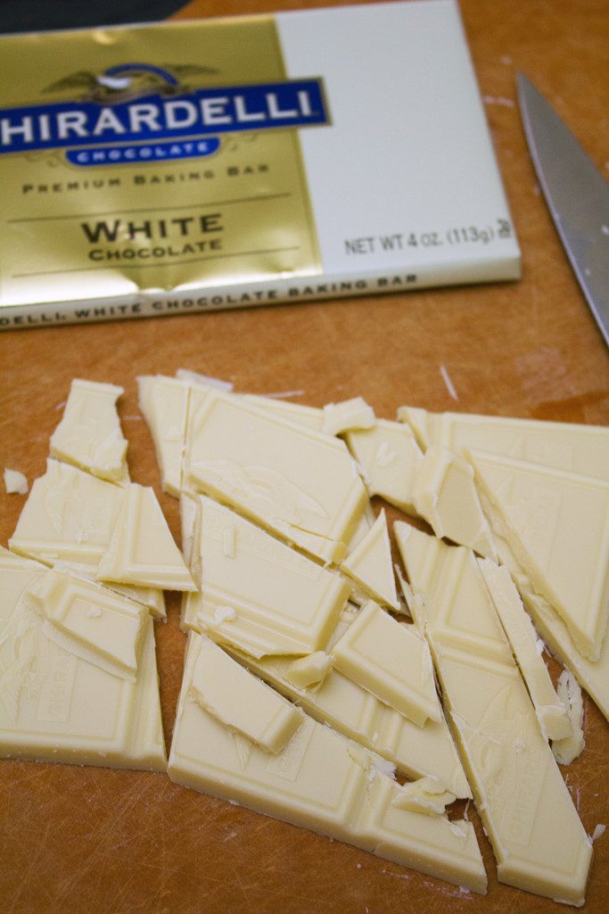 White chocolate coarsely chopped on cutting board
