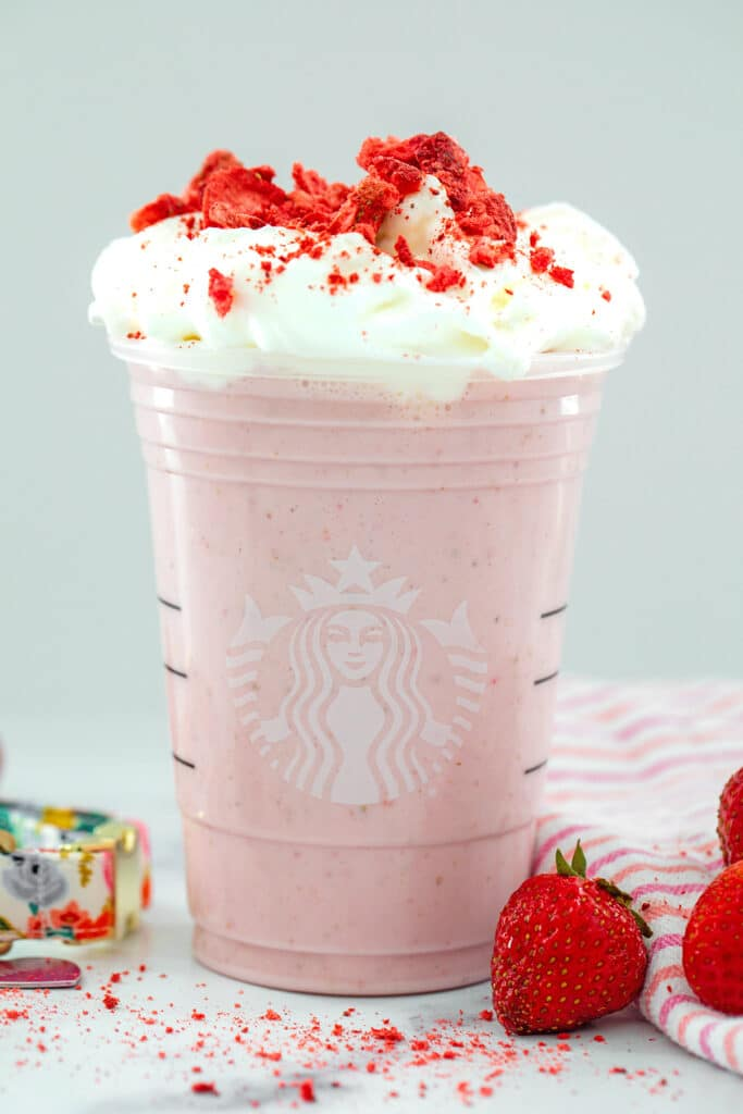 Head-on view of a homemade Starbucks' Strawberry Puppuccino topped with whipped cream and crushed freeze-dried strawberries with strawberries all around
