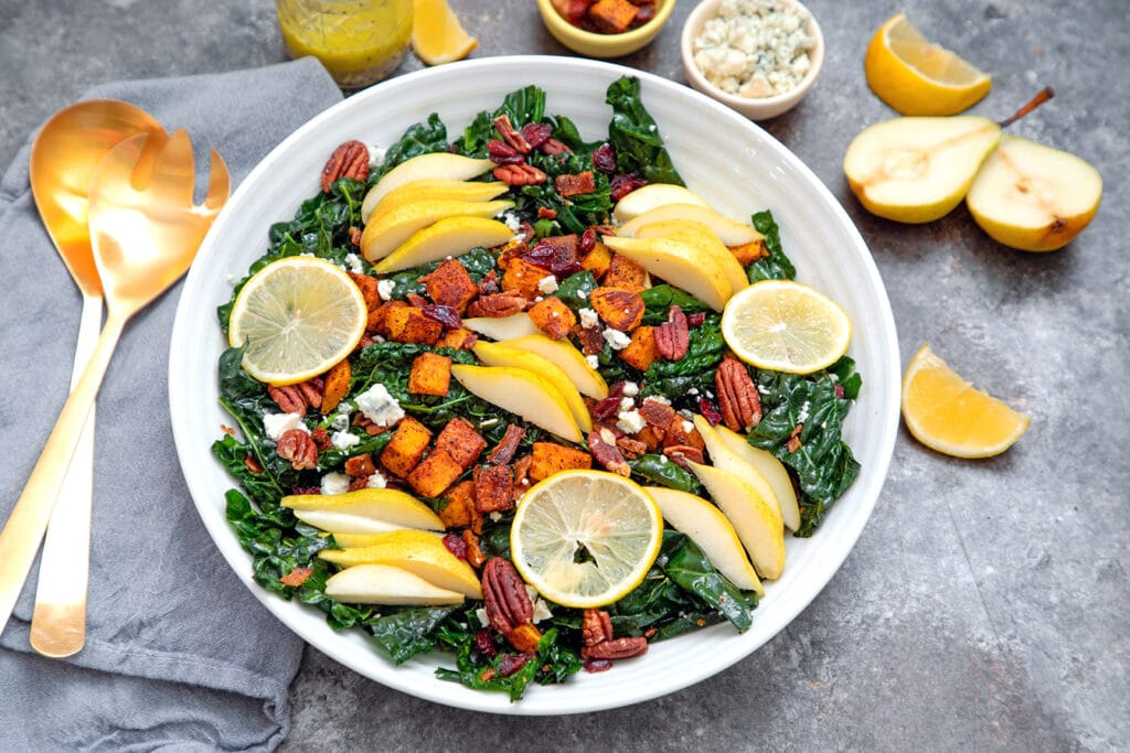 Landscape view of winter kale salad with pears, butternut squash, pecans, gorgonzola cheese, and sliced meyer lemons with ingredients in background
