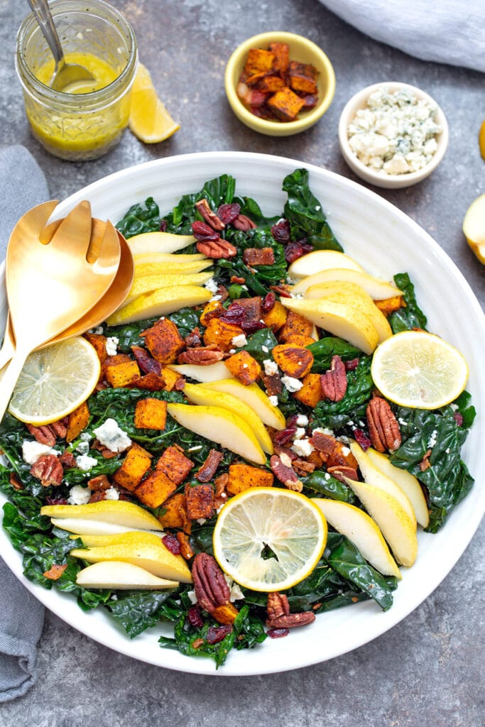 Overhead view winter kale salad in large white bowl with butternut squash, pears, gorgonzola, pecans, and sliced meyer lemons with jar of dressing in background