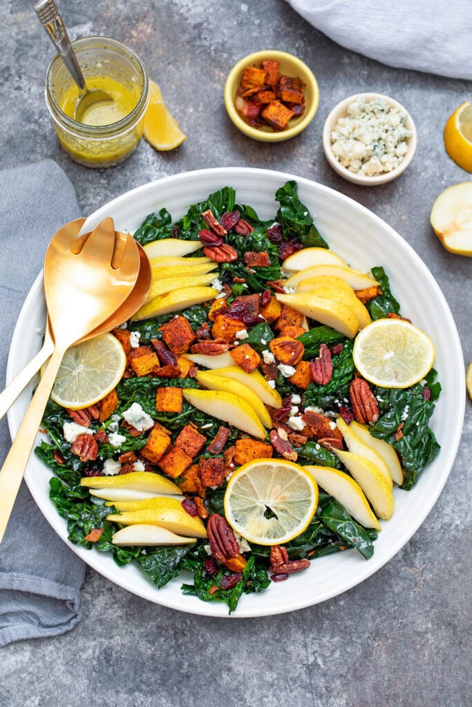 Bird's eye view of winter kale salad in large white bowl topped with butternut squash, pears, gorgonzola cheese, pecans, and sliced meyer lemons with gold utensils, jar of dressing, and bowls of other ingredients in background