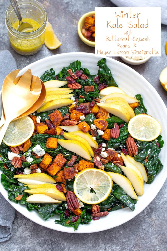 Overhead view of winter kale salad in large white bowl with butternut squash, pears, gorgonzola, pecans, and sliced meyer lemons with jar of dressing in background and recipe title at top
