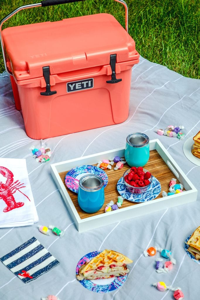Close-up of picnic spread featuring coral Yeti cooler on a grey blanket with a tray with blue cups, lobster napkins, and plates with waffles and waffles sandwiches