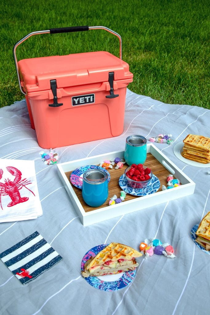 Picnic spread featuring coral Yeti cooler on a grey blanket with a tray with blue cups, lobster napkins, and plates with waffles and waffles sandwiches