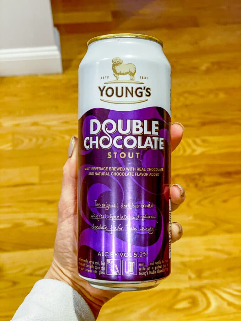 Hand holding a can of Young's Double Chocolate Stout