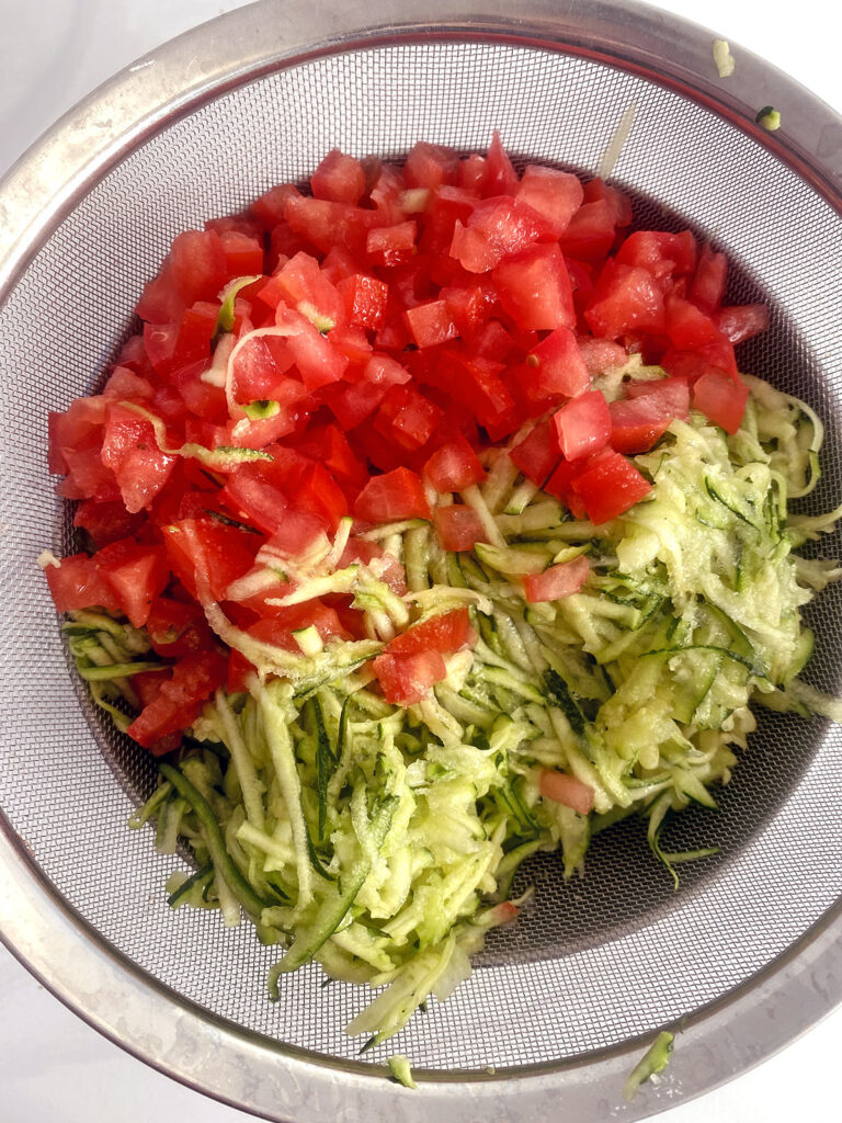 Shredded zucchini and chopped tomatoes in strainer