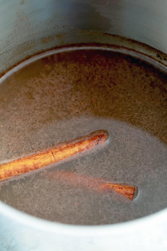 apple cider cinnamon stick glaze for ham being made in a saucepan