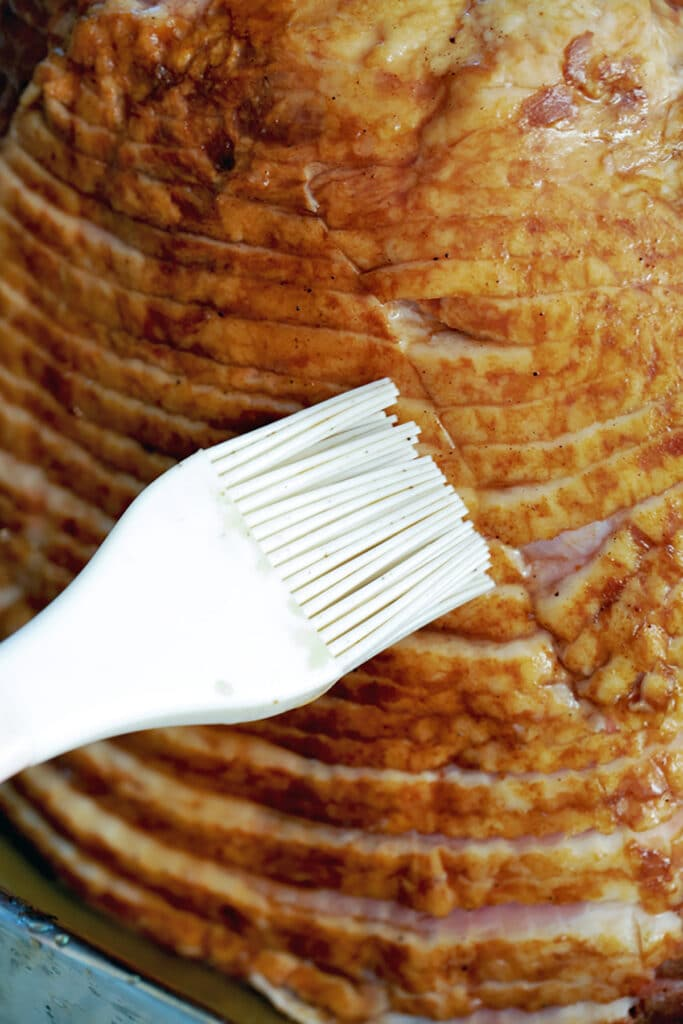 Close-up of spiral cut ham being brushed with glaze