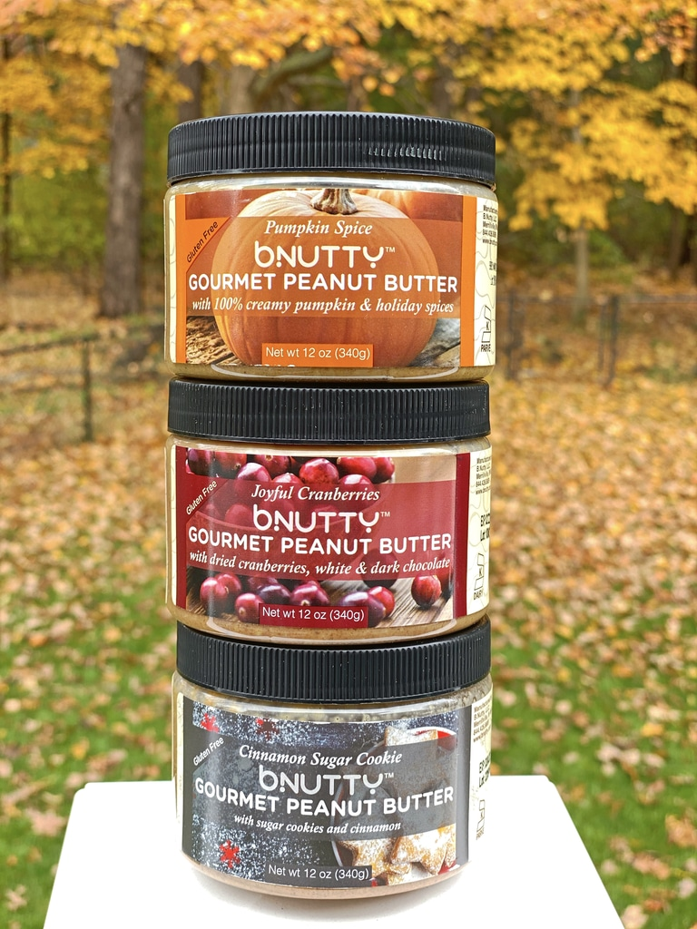Stack of B.Nutty Peanut Butter in three flavors (pumpkin spice, cranberry, and cinnamon sugar cookie)
