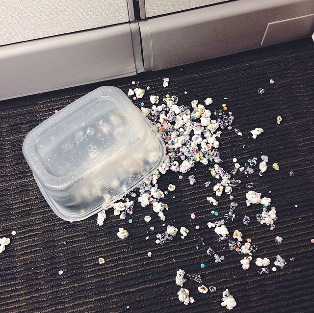 Tupperware of Oreo funfetti popcorn fallen on the ground with popcorn everywhere