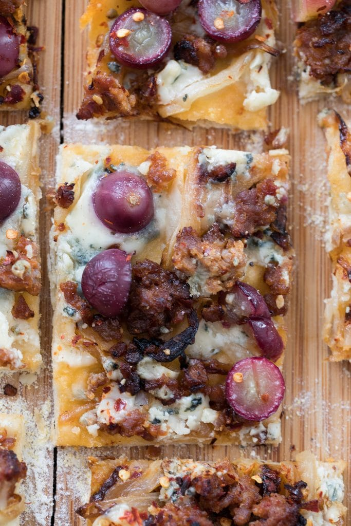 A close-up shot from above of a square slice of sausage, grape, and gorgonzola flatbread pizza