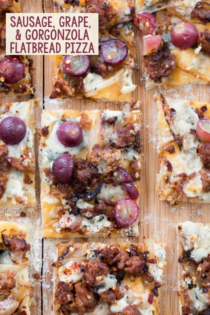 "Thin crust flatbread pizza cut into squares and topped with sausage, grapes, onions, and gorgonzola cheese with text in the corner that says ""Sausage, Grape, and Gorgonzola Flatbread"""
